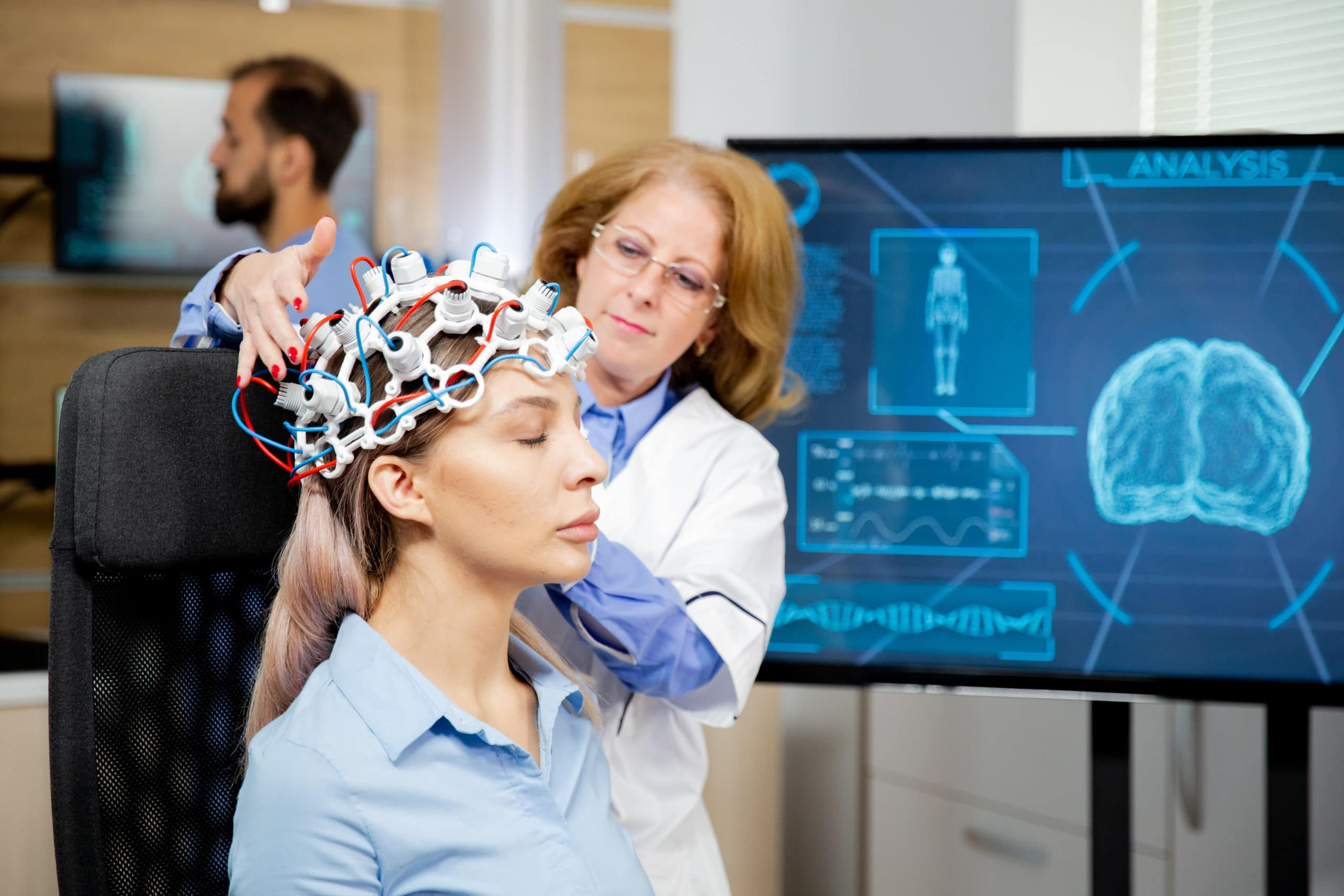 Doctor arranging neurology scanning headset for tests on a female patient. Scanning machine
