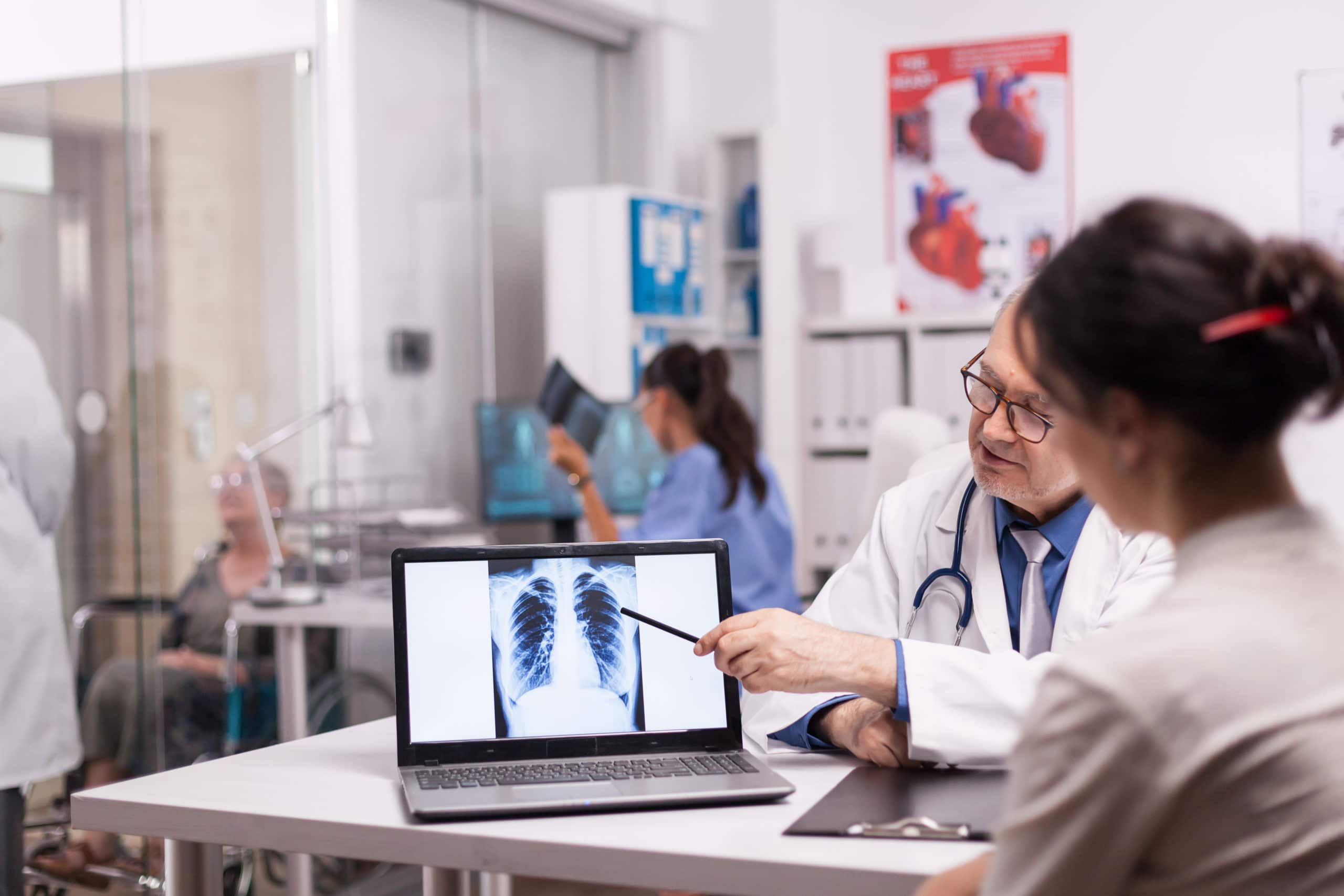 Mature doctor pointing at patient lungs ct scan on laptop during medical visit in hospital office. Medic in white coat discussing with disabled senior woman in wheelchair and nurse in holding x-ray.