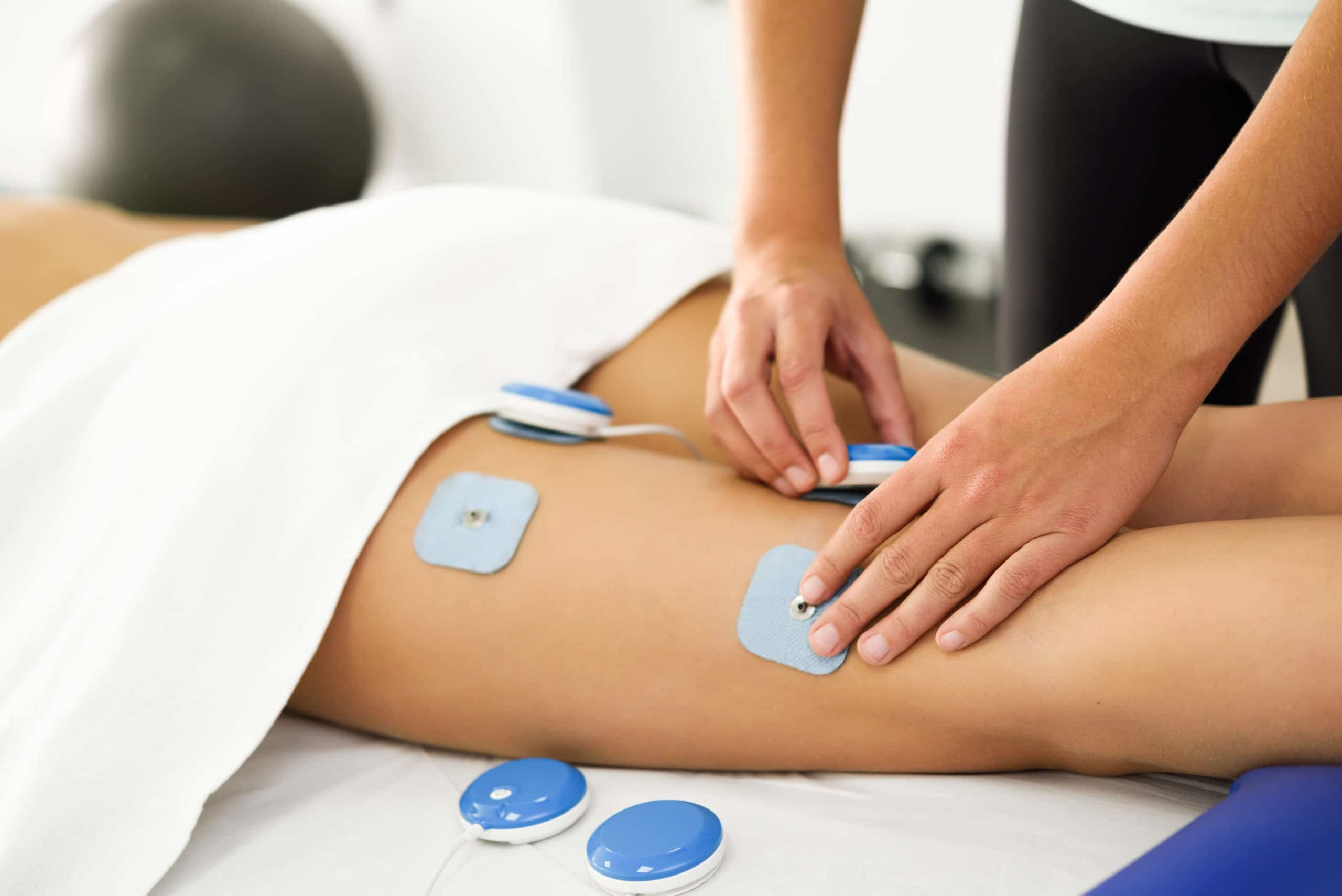 Physiotherapist applying electro stimulation in physical therapy to a young woman. Medical check at the leg in a physiotherapy center.